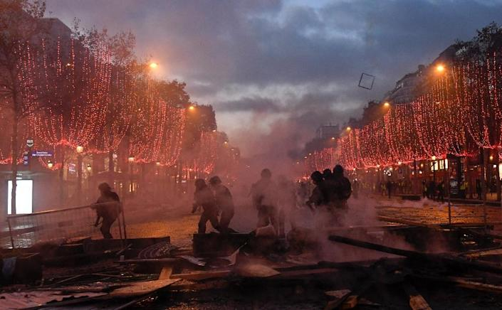 The famed Champs-Elysees, decked out in twinkling Christmas lights, was left shrouded in smoke from tear gas and fires (AFP Photo/Bertrand GUAY)