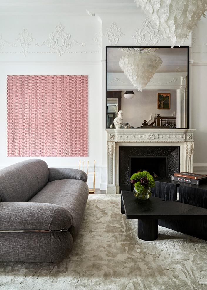 "<div class=""caption""> To decorate the living room, which features a new fireplace with an antique French mantel, Gillian Dubin chose a combination of Italian designs from the '60s and '70s and contemporary geometric shapes. The voluminous gray sofa, <a href=""https://mattermatters.com/products/sesann"" rel=""nofollow noopener"" target=""_blank"" data-ylk=""slk:a reissue"" class=""link rapid-noclick-resp"">a reissue</a> of a Gianfranco Frattini model from 1970, was paired with a sculptural two-piece coffee table in a new design by <a href=""https://apparatusstudio.com/"" rel=""nofollow noopener"" target=""_blank"" data-ylk=""slk:Apparatus Studio"" class=""link rapid-noclick-resp"">Apparatus Studio</a>. The Murano leaf chandelier was made in the '60s in the style of Seguso Adesso. Next to the fireplace is a powder-coated galvanized steel artwork by <a href=""https://davinasemo.net"" rel=""nofollow noopener"" target=""_blank"" data-ylk=""slk:Davina Semo"" class=""link rapid-noclick-resp"">Davina Semo</a>. </div>"