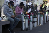 People wait to refill oxygen tanks for relatives sick with COVID-19 in the Iztapalapa district of Mexico City, on Tuesday, Jan. 26, 2021. The city is offering free oxygen refills for patients with COVID-19. (AP Photo/Marco Ugarte)