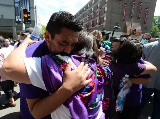 Joyce Echaquan's husband, CarolDubé, left, hugs family members at a rally in Trois-Rivieres, Que., on Wednesday.   (Ryan Remiorz/The Canadian Press - image credit)