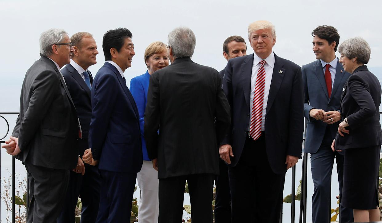 U.S. President Donald Trump gathers with (from left to right) European Commission President Jean-Claude Juncker, European Council President Donald Tusk, Japanese Prime Minister Shinzo Abe, German Chancellor Angela Merkel, Italian Prime Minister Paolo Gentiloni, French President Emmanuel Macron, Canadian Prime Minister Justin Trudeau and British Prime Minister Theresa May as they attend the G7 summit in Taormina, Sicily, on May 26, 2017.