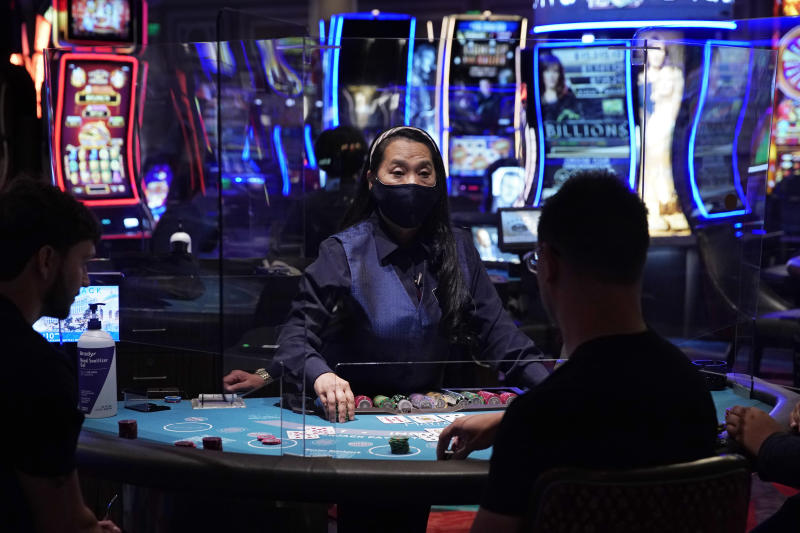 People play blackjack at the reopening of the Bellagio hotel and casino Thursday, June 4, 2020, in Las Vegas. Casinos in Nevada were allowed to reopen on Thursday for the first time after temporary closures as a precaution against the coronavirus. (AP Photo/John Locher)
