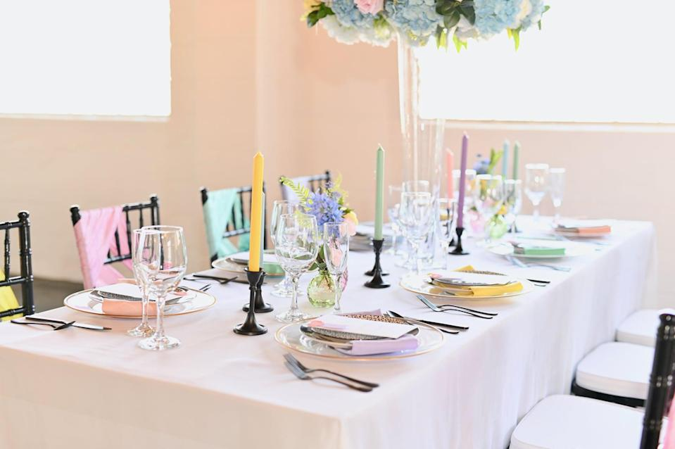 <p>Notice how the candle holders, utensils, and chairs are the same uniform color at this ceremony. These striking accents stand out and give the table setting a regal finish. To copy this look, simply paint select decor pieces the color you want and buy colored silverware to match.</p>