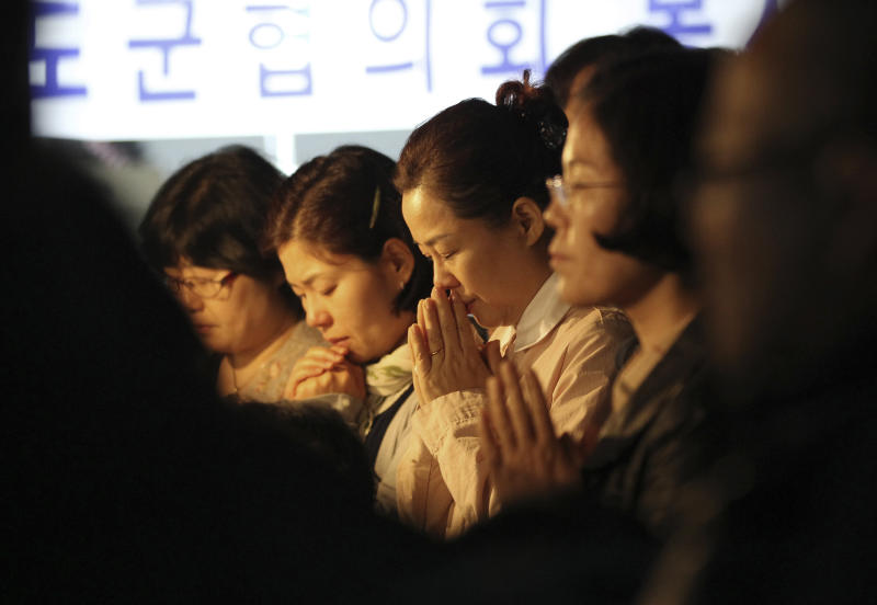 Relatives of missing passengers aboard the sunken ferry Sewol pray to wish for safe return of their family members during an annual Easter service in Jindo, South Korea, Sunday, April 20, 2014. After more than three days of frustration and failure, divers on Sunday finally found a way into the submerged ferry off South Korea's southern shore, discovering more than a dozen bodies inside the ship and pushing the confirmed death toll to over four dozens, officials said. (AP Photo/Ahn Young-joon)