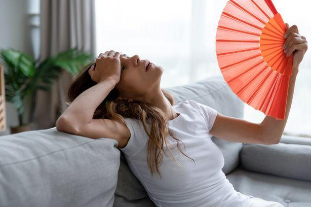 Side view exhausted young biracial girl using paper waver, suffering from hot summer weather or high temperature at home. Unhappy overheated millennial mixed race woman feeling uncomfortable indoors. (Photo: fizkes via Getty Images/iStockphoto)