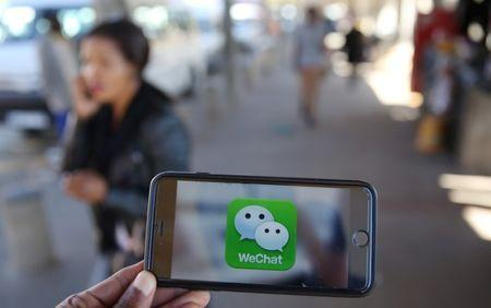A WeChat logo is displayed on a mobile phone as a woman walks past as she talks on her mobile phone at a taxi rank in this picture illustration taken July 21, 2016. REUTERS/Siphiwe Sibeko/Illustration