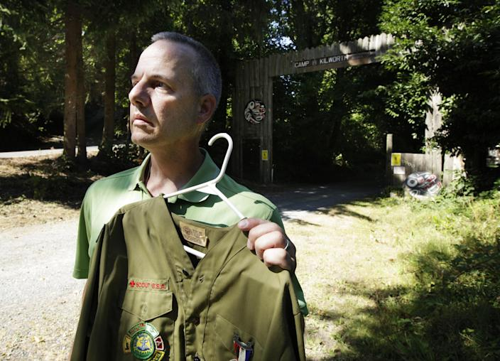 """In this Thursday, Aug. 16, 2012 photo, Boy Scout abuse victim Tom Stewart poses for a photo with his old Scout uniform outside the Boy Scout Camp Kilworth in Federal Way, Wash. Former Boy Scouts still struggle to cope with the abuse they suffered at the hands of Scout leaders, and those who are willing to tell the stories of their abuse have come to feel abandoned by an organization considered a pillar of American society. """"There are so many victims who have suffered in silence. Marriages and relationships with their kids have suffered,"""" said Stewart, a 46-year-old engineer for Boeing. (AP Photo/Ted S. Warren)"""