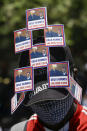 A supporter of former Haitian President Jean-Bertrand Aristide wears stickers of him and late South African President Nelson Mandela, as he awaits Aristide's arrival from Cuba, where he underwent medical treatment, near the airport in Port-au-Prince, Haiti, Friday, July 16, 2021. Aristide's return adds a potentially volatile element to an already tense situation in a country facing a power vacuum following the July 7 assassination of President Jovenel Moïse. (AP Photo/Joseph Odelyn)