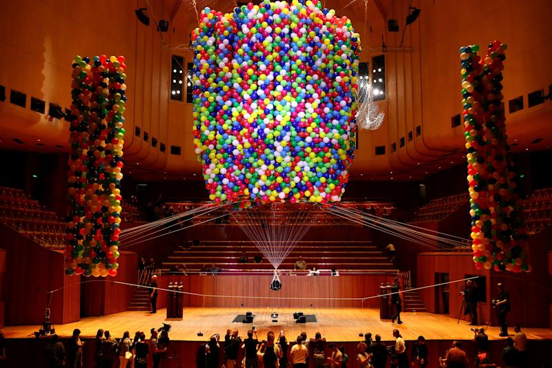 Austrian British artist Noëmi Lakmaier is seen suspended by 20,000 helium-filled balloons inside of the Sydney Opera House on Sunday. (Cameron Spencer via Getty Images)