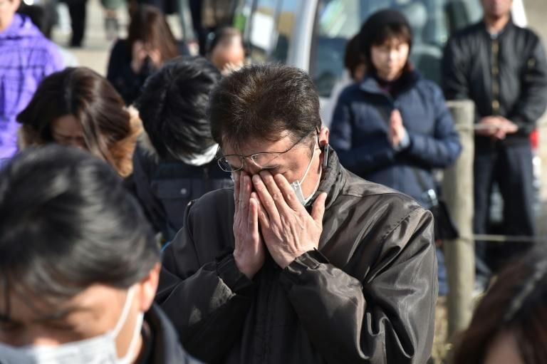People offer a silent prayer to mark six years since a deadly earthquake, tsunami and nuclear disaster devastated Japan's northeastern coast