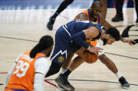 Denver Nuggets guard Jamal Murray, center, picks up a loose ball as Phoenix Suns forward Jae Crowder, front, and guard Chris Paul defend during the second half of an NBA basketball game Friday, Jan. 1, 2021, in Denver. (AP Photo/David Zalubowski)