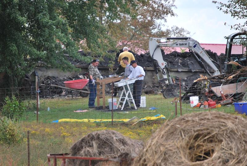 Workers are still on the job Thursday, Sept. 27, 2012, near Shelbyville, Tenn., at the site of a house fire that where an elderly couple and two young children lived. Authorities were searching the debris for the remains of the two missing children, 9-year-old Chloie Leverette and 7-year-old Gage Daniel. The two children were initially believed to have perished in the intense fire, which firefighters battled overnight Sunday and early Monday. (AP Photo/Kristin M. Hall)