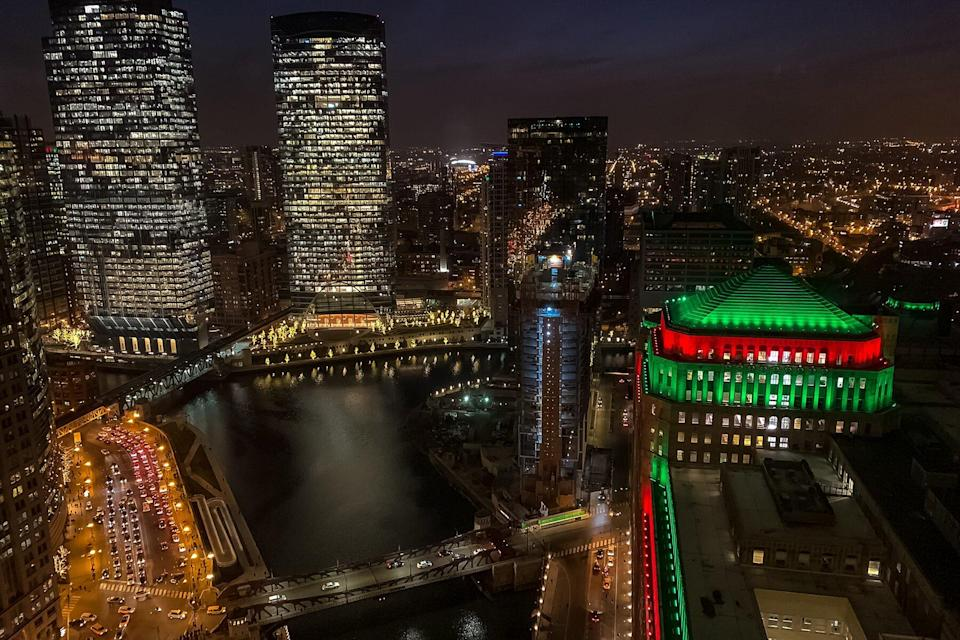 City lights, including Christmas/holiday lights, are illuminated over Chicago River in December