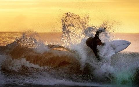 A surfer in action during sunrise at Tynemouth on the north east coat - Credit: Owen Humphreys/PA