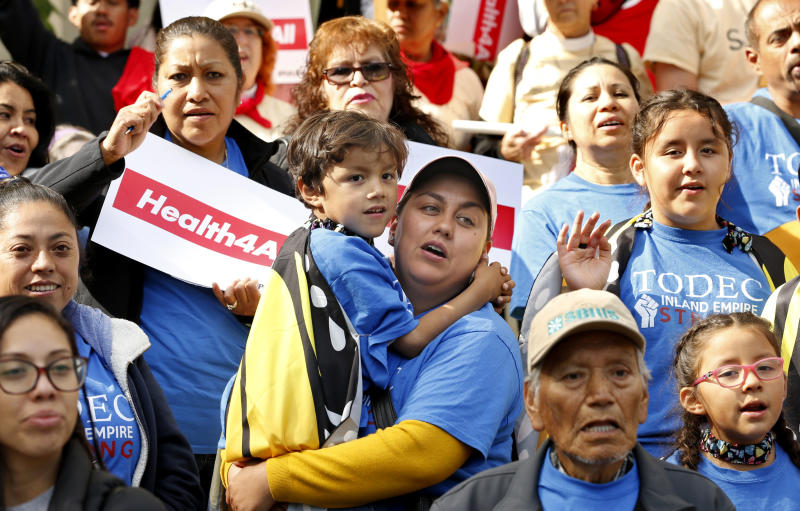 FILE - In this May 20, 2019, file photo, Oralia Sandoval, center, holds her son Benjamin, 6, as she participates in an Immigrants Day of Action rally in Sacramento, Calif. California will become the first state to pay for some adults living in the country illegally to have full health benefits as the solidly liberal bastion continues to distance itself from President Donald Trump's administration. (AP Photo/Rich Pedroncelli, File)