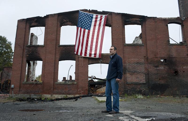 "Matt Bevin stands at the site of his family's factory destroyed by fire in East Hampton, Conn., Wednesday, Oct. 3, 2012. The 180-year-old New England company that made the tiny bell that tinkles every time an angel gets its wings in the holiday classic ""It's a Wonderful Life"" is resuming production months after the factory was destroyed in a fire. (AP Photo/Jessica Hill)"