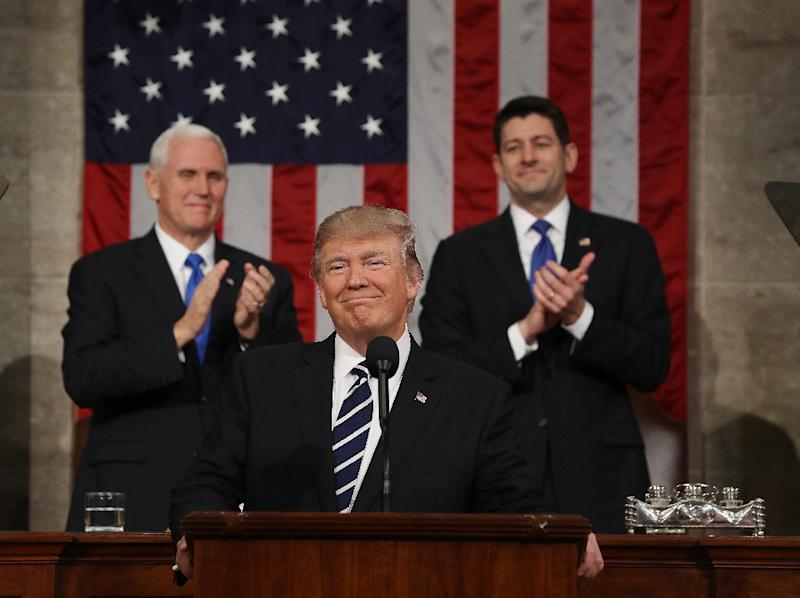 US Vice President Mike Pence (L) and Speaker of the House Paul Ryan (R) applaud as President Donald Trump (C) arrives to deliver his first address to a joint session of Congress from the floor of the House of Representatives on 28 February 2017 (AFP Photo/JIM LO SCALZO)