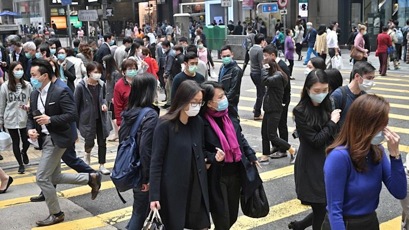 Pedestrians wear face masks, as a precautionary measure against the COVID-19 coronavirus, in Hong Kong on March 12, 2020