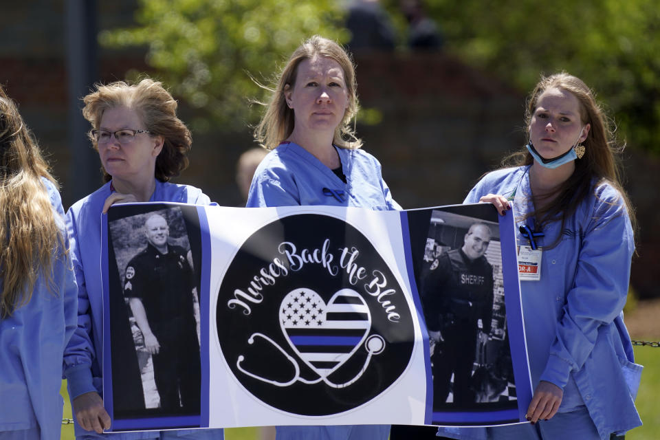 Nurses watch as a processional approaches the Holmes Convocational Center for the funeral services of Watauga County Sheriff's Deputies Sgt. Chris Ward and K-9 Deputy Logan Fox in Boone, N.C., Thursday, May 6, 2021. The two deputies were killed in the line of duty. (AP Photo/Gerry Broome)
