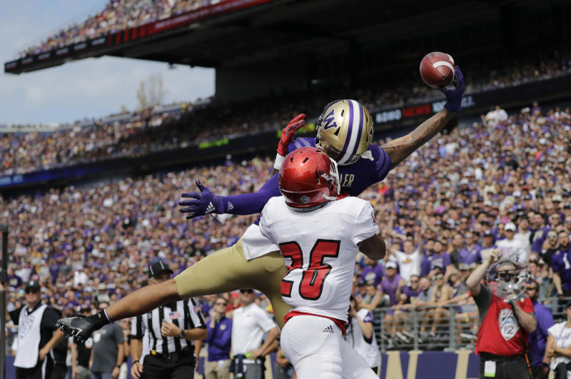 Washington's Aaron Fuller makes a one-handed catch for a touchdown over Eastern Washington's Darreon Moore (26) in the first half of an NCAA college football game Saturday, Aug. 31, 2019, in Seattle. (AP Photo/Elaine Thompson)
