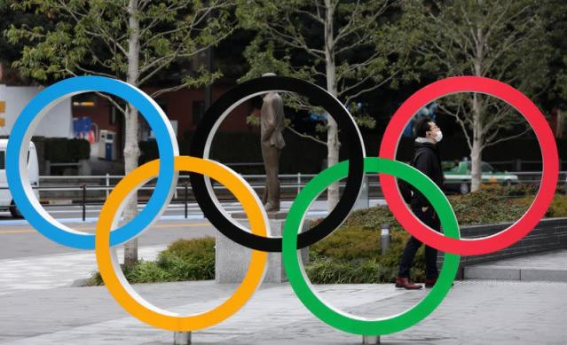 Man wearing protective face mask is seen through The Olympic rings in front of the Japan Olympics Museum in Tokyo