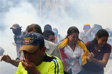 Venezuelas opposition leader Maria Corina Machado runs away from tear gas after she tries to take her seat at national assembly in Caracas