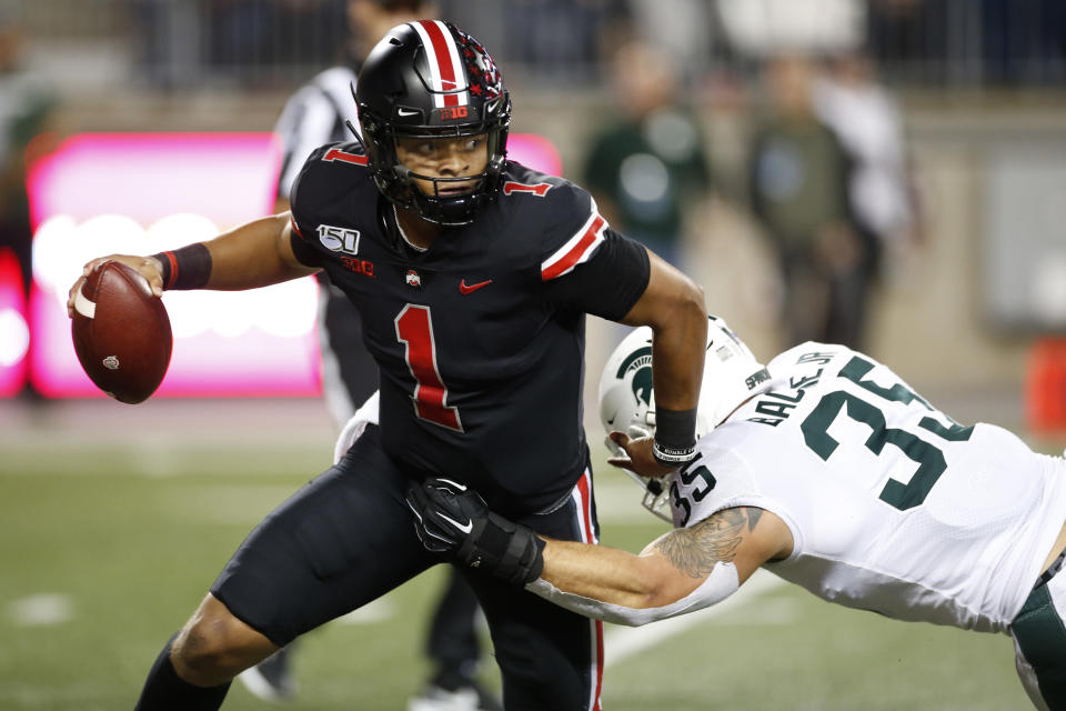 Ohio State quarterback Justin Fields, left, escapes the grasp of Michigan State linebacker Joe Bachie during the first half of an NCAA college football game Saturday, Oct. 5, 2019, in Columbus, Ohio. (AP Photo/Jay LaPrete)
