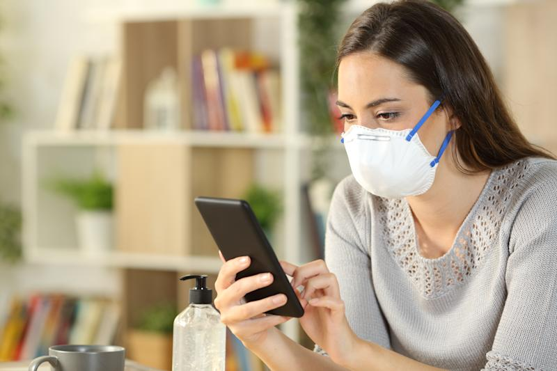 Serious woman with protective mask due coronavirus using smart phone sitting on the livingroom at home
