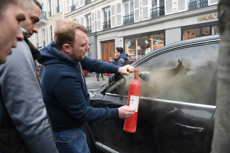 A man tries to extinguish a fire inside a car on the sidelines of a demonstration in Paris on Thursday