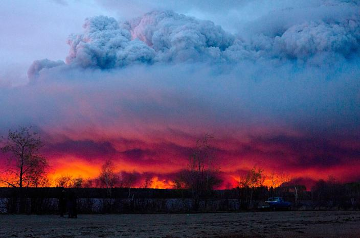 <p>MAY 4, 2016 — A wildfire moves towards the town of Anzac from Fort McMurray, Alberta. Alberta declared a state of emergency Wednesday as crews frantically held back wind-whipped wildfires. Unseasonably hot temperatures combined with dry conditions have transformed the boreal forest in much of Alberta into a tinder box. (Jason Franson/The Canadian Press via AP) </p>
