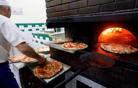 A staff member prepares pizza Margherita at L'Antica Pizzeria da Michele in Naples