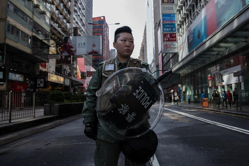 A Hong Kong riot policewoman stands on a cordoned-off street on February 9, 2016 (AFP Photo/Dale de la Rey)