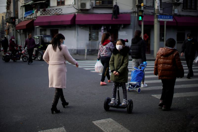 A girl wearing a mask rides a smart self-balancing scooter on a street in downtown Shanghai