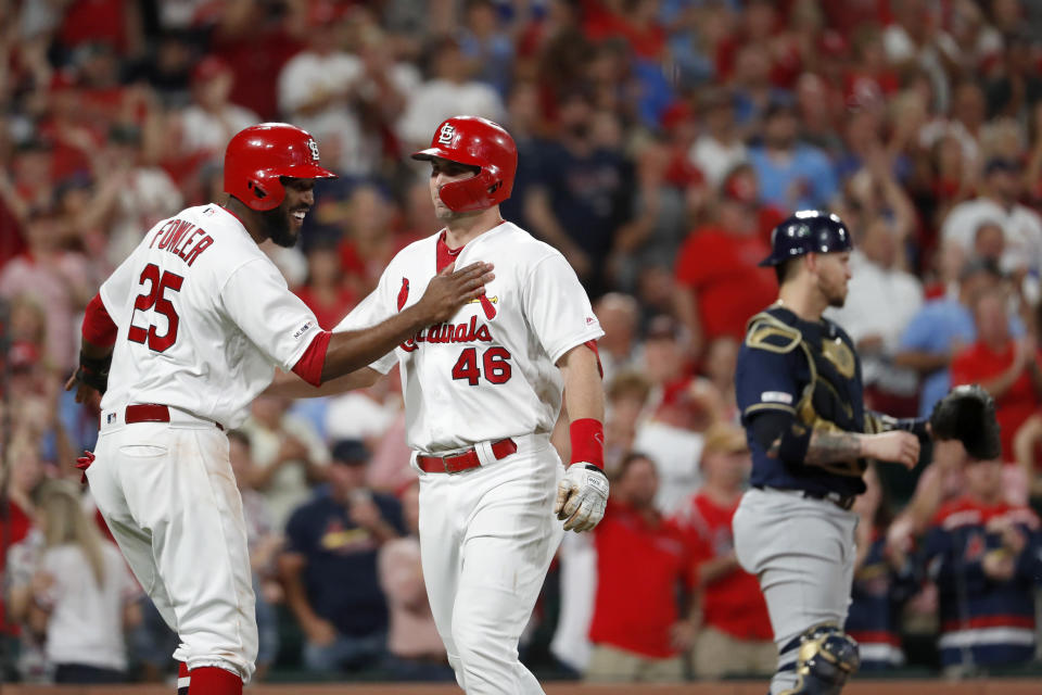 St. Louis Cardinals' Paul Goldschmidt (46) is congratulated by teammate Dexter Fowler (25) after hitting a three-run home run as Milwaukee Brewers catcher Yasmani Grandal, right, stands at the plate during the sixth inning of a baseball game Friday, Sept. 13, 2019, in St. Louis. The home run was the second of the game for Goldschmidt. (AP Photo/Jeff Roberson)