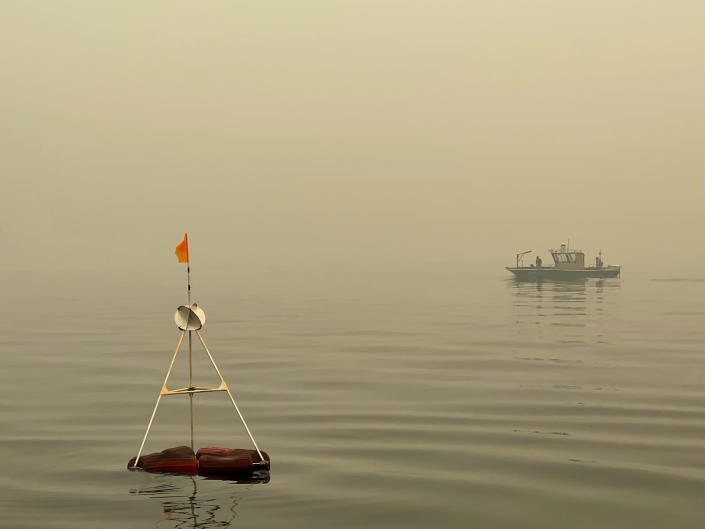 This photo provided by UC Davis shows a buoy in Lake Tahoe keeps a collection bucket in place that researchers have positioned to measure particles and gauge wildfire's effect on the clarity of Lake Tahoe in Lake Tahoe, Calif., on Aug.23, 2021. Scientists say it's too soon to draw definite conclusions about the lasting damage that record-setting wildfires will have on Lake Tahoe. (Brandon Berry/UC Davis via AP)
