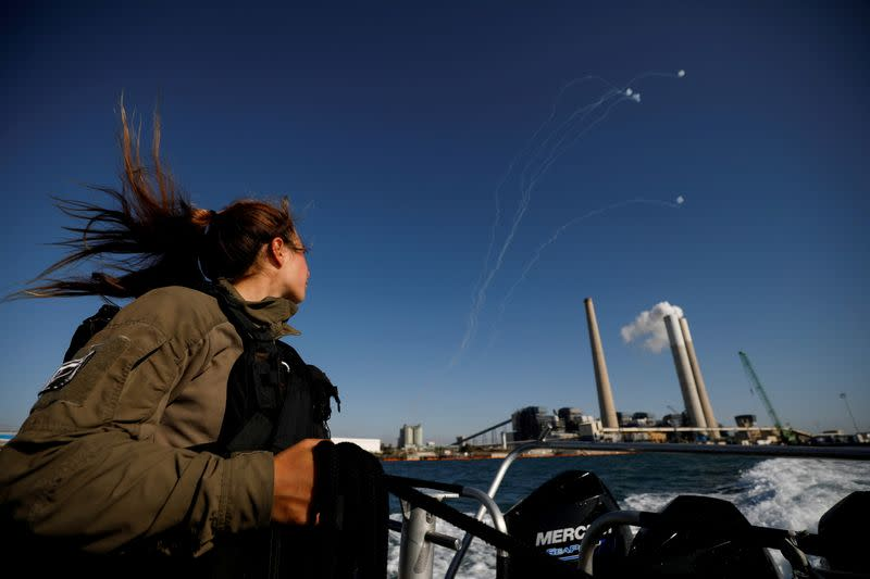 FILE PHOTO: An Israeli soldier looks on as Israel's Iron Dome anti-missile system intercept rockets launched from the Gaza Strip towards Israel, as it seen from a naval boat patrolling the Mediterranean Sea