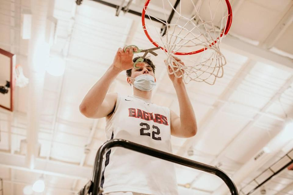 Lincoln Charter senior center Carter Seitz helps cut down the net after the school won the 1A Western Regional Final on Tuesday with a 64-54 victory over Mount Airy.