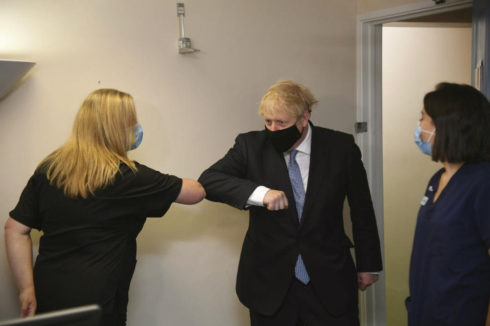 Britain's Prime Minister Boris Johnson elbow bumps a member of staff, during a visit to Tollgate Medical Centre in Beckton, East London, Friday July 24, 2020. (Jeremy Selwyn/Pool Photo via AP)