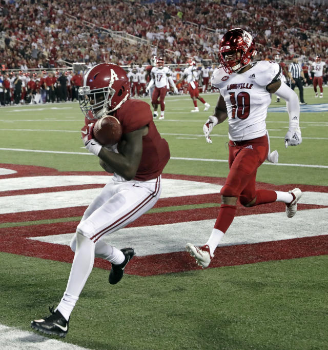 Alabama wide receiver Jerry Jeudy, left, catches a 25-yard touchdown pass in front of Louisville cornerback Rodjay Burns (10) during the first half of an NCAA college football game Saturday, Sept. 1, 2018, in Orlando, Fla. (AP Photo/John Raoux)
