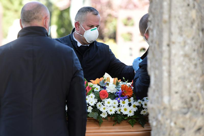 Undertakers wearing a face mask unload a coffin out of a hearse on March 16, 2020 at the Monumental cemetery of Bergamo, Lombardy, as burials of people who died of the new coronavirus are being conducted at the rythm of one every half hour. (Photo by Piero Cruciatti / AFP) (Photo by PIERO CRUCIATTI/AFP via Getty Images)