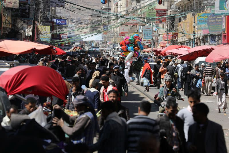 People walk at a street market in Sanaa