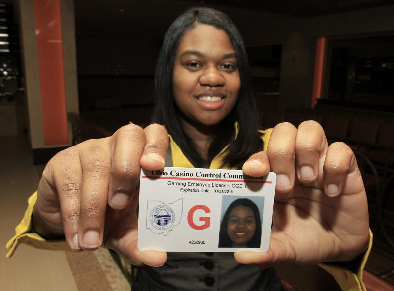 Taneshia Pitts, 28, holds up the first gaming employee license at the Horseshoe Casino Cleveland Thursday, April 5, 2012. The commission has approved more than 1,100 licenses and is investigating more than 500 other applicants. The Cleveland casino opens during the week of May 14, Toledo's will open two weeks later and casinos in Cincinnati and Columbus will open next year. (AP Photo/Tony Dejak)