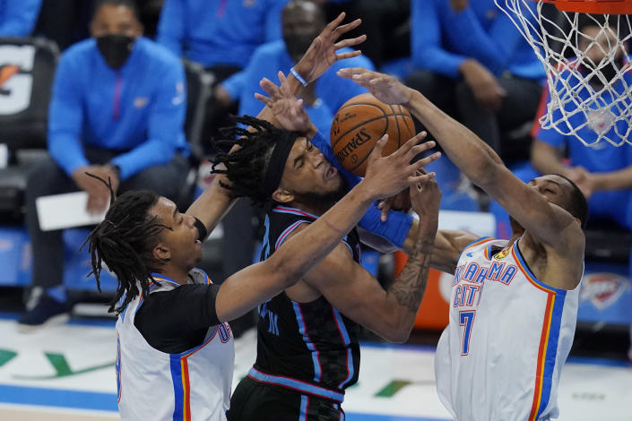 Sacramento Kings forward Marvin Bagley III, center, reaches for a rebound with Oklahoma City Thunder center Moses Brown, left, and forward Darius Bazley (7) in the second 117half of an NBA basketball game Tuesday, May 4, 2021, in Oklahoma City. (AP Photo/Sue Ogrocki)