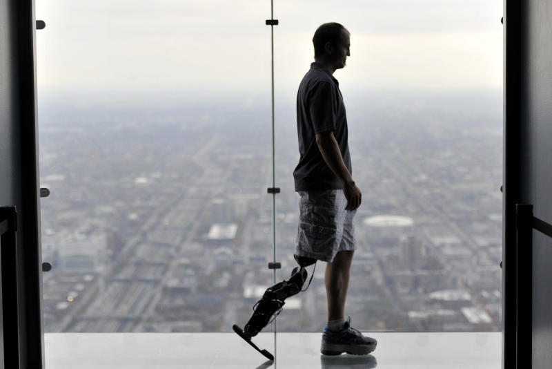 """In this Oct. 25, 2012 photo, Zac Vawter, fitted with an experimental """"bionic"""" leg, is silhouetted on the Ledge at the Willis Tower in Chicago. Vawter is training for the world's tallest stair-climbing event where he'll attempt to climb 103 flights to the top of theWillis Tower using the new prosthesis. (AP Photo/Brian Kersey)"""