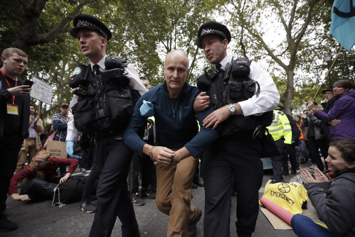 Police officers lead a handcuffed protestor away after climate protestors blocked a road in central London Monday, Oct. 7, 2019. (Photo: Matt Dunham/AP)
