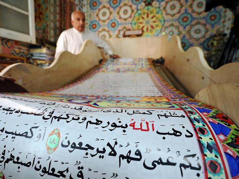 Saad Mohammed rolls down the handwritten Quran he hopes will earn a place in the Guinness Book of Records (Reuters)
