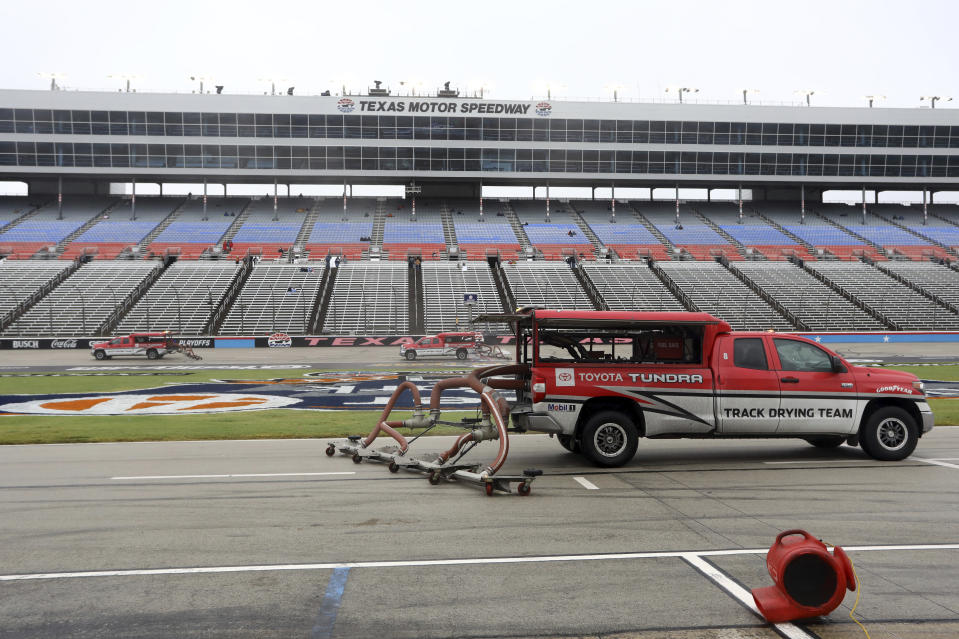 Trucks dry the track in an attempt to resume a NASCAR Cup Series auto race after morning rain prevented the  rescheduled start at Texas Motor Speedway in Fort Worth, Texas, Monday, Oct. 26, 2020. (AP Photo/Richard W. Rodriguez)