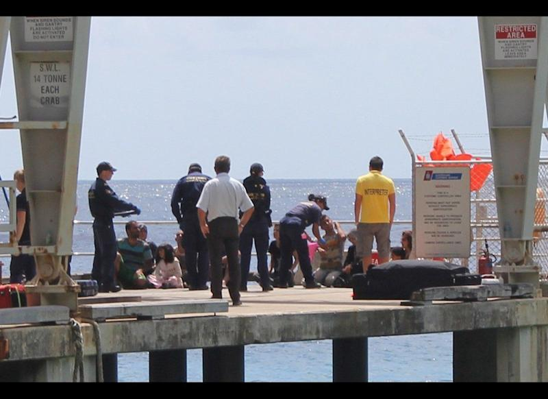 Australian authorities check newly arrived refugees on a dock on Australia's Christmas Island. (Oliver White/Jesuit Refugee Service)