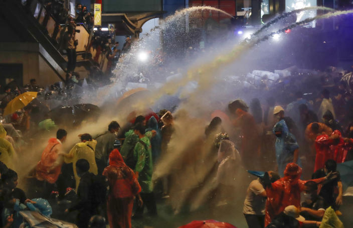 Pro democracy demonstrators face water canons as police try to clear the protest venue in Bangkok, Thailand, Friday, Oct. 16, 2020. Thailand prime minister has rejected calls for his resignation as his government steps up efforts to stop student-led protesters from rallying in the capital for a second day in defiance of a strict state of emergency. (AP Photo/Sakchai Lalit)
