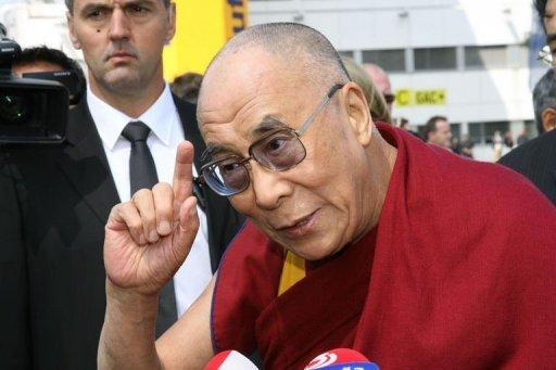 Tibet's exiled spiritual leader the Dalai Lama (C) speaks on arrival at the airport in Vienna